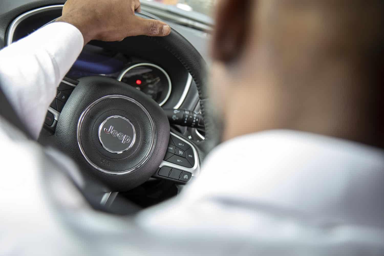 Motorista dirigindo um carro da Jeep